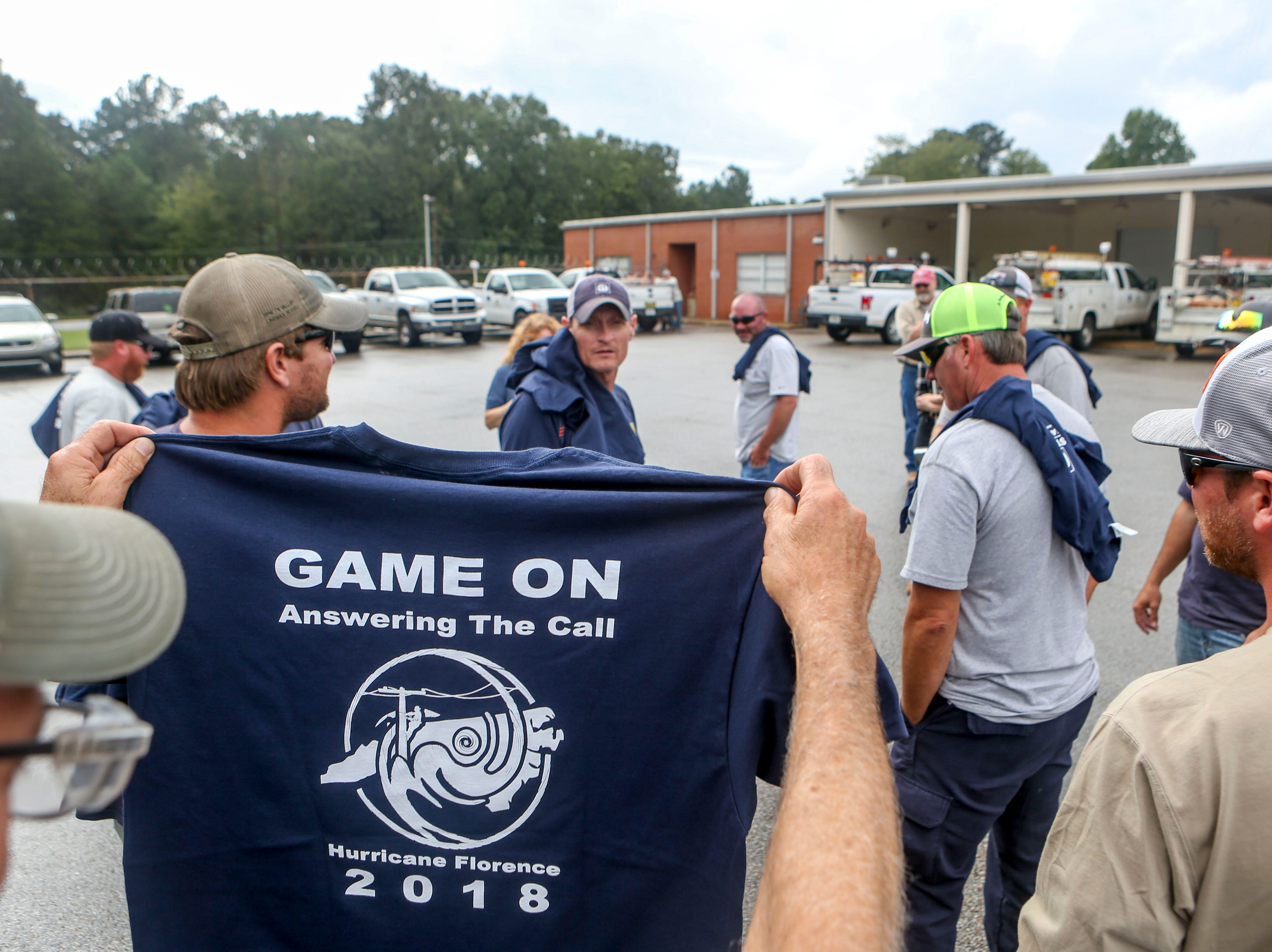 A linemen that was dispatched to assist with recovery efforts after Hurricane Florence holds up a t-shirt made for the team that returned at Southwest Tennessee Electric in Jackson, Tenn., Monday, Sept. 24, 2018.