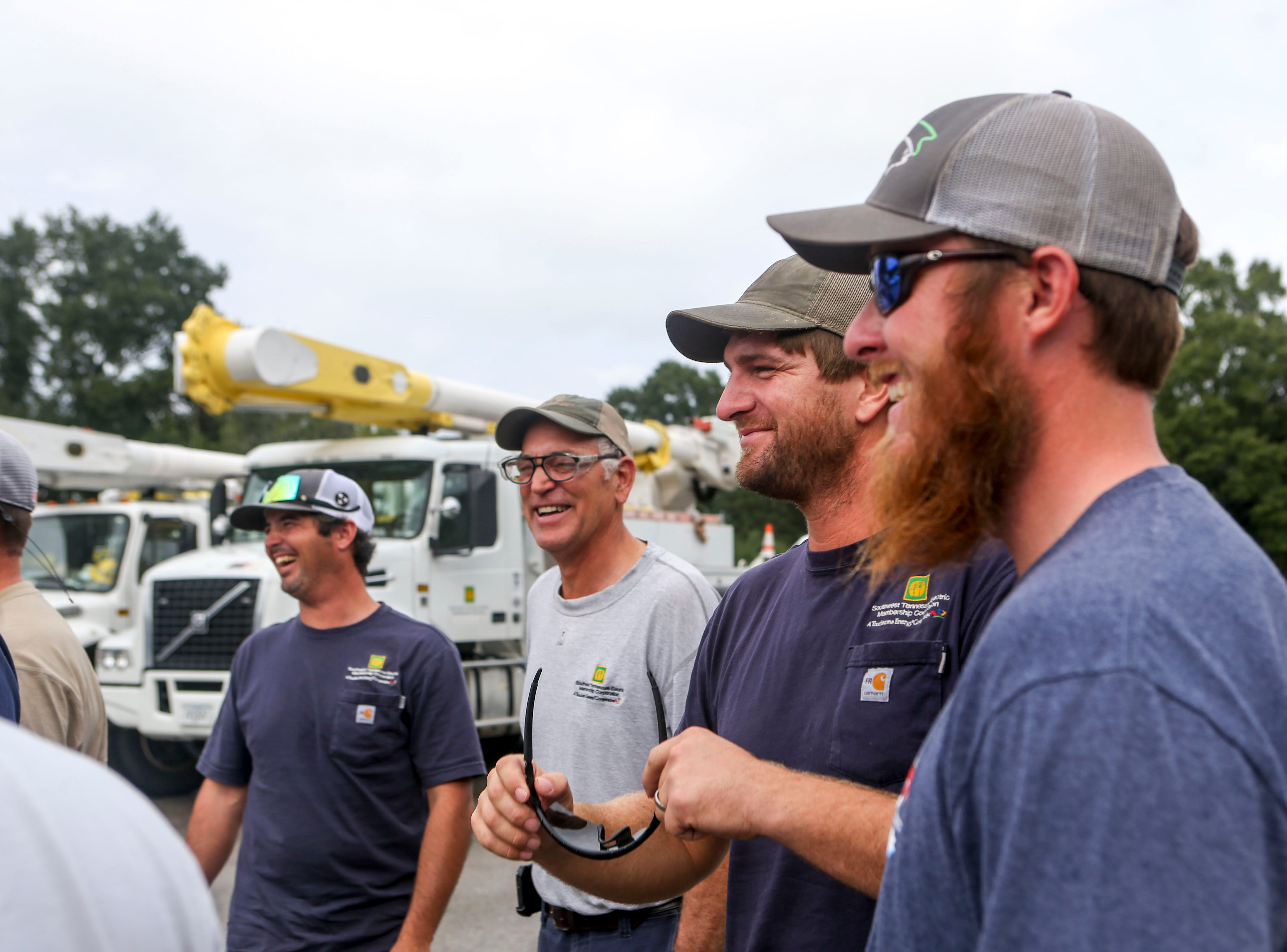 Linemen dispatched to North Carolina joke around while talking with management after returning to Southwest Tennessee Electric in Jackson, Tenn., Monday, Sept. 24, 2018.