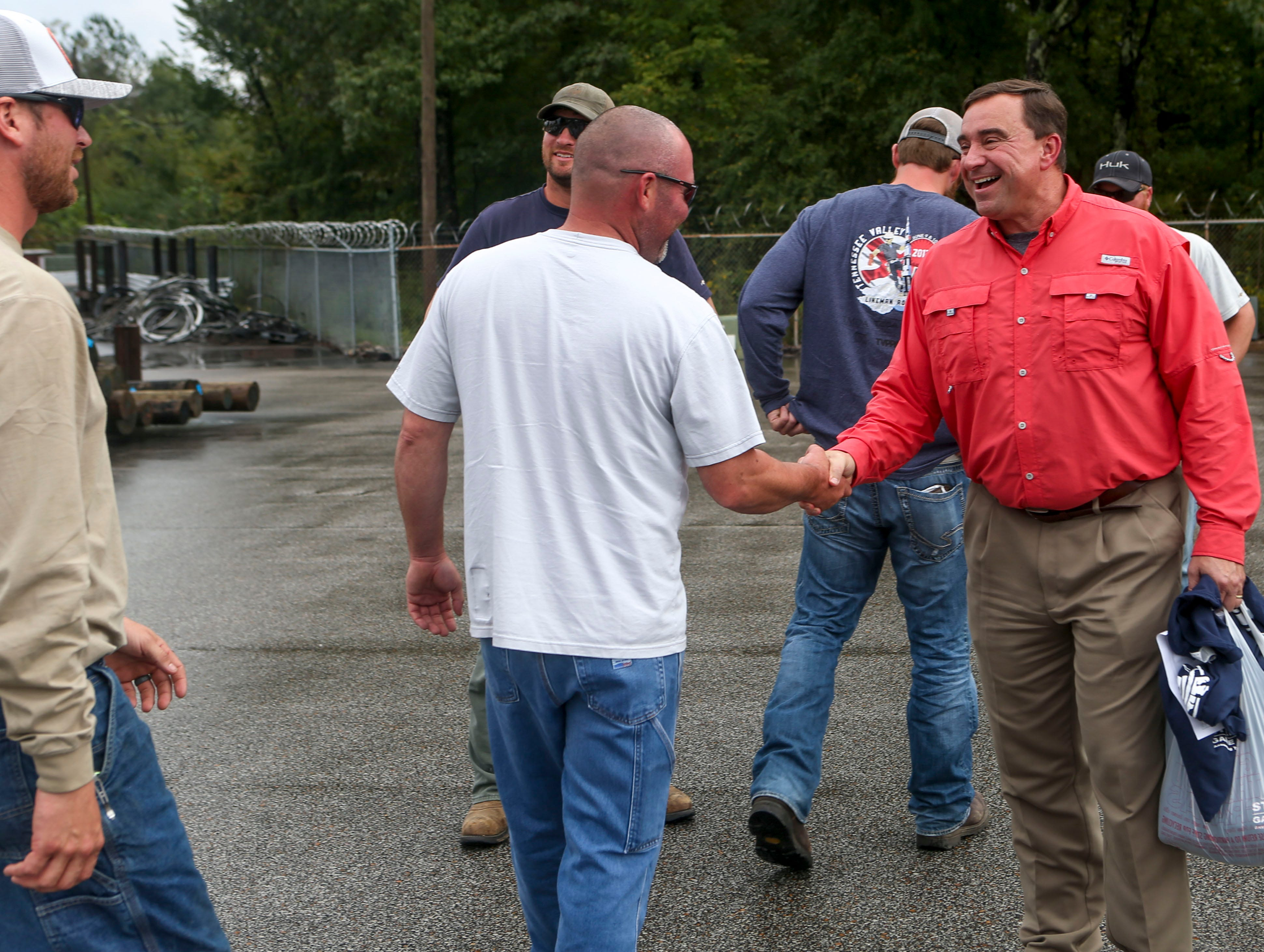 Vice President of operations Mike Russell shakes hands with a team of linemen arriving home that had been dispatched to assist areas affected by Hurricane Florence at Southwest Tennessee Electric in Jackson, Tenn., Monday, Sept. 24, 2018.