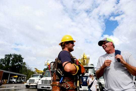 Linemen talk with one another after grabbing gear from their work trucks at Southwest Tennessee Electric in Jackson, Tenn., Monday, Sept. 24, 2018.