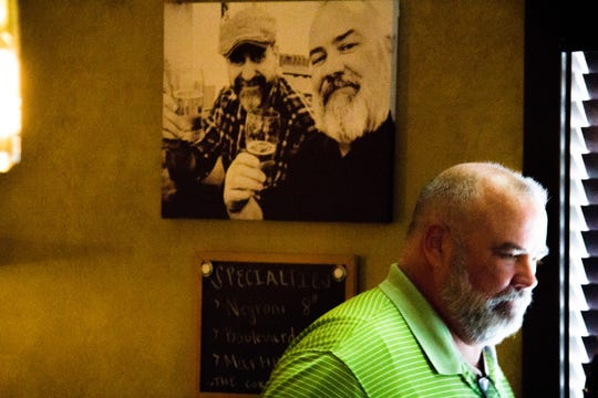 John Harbison stands at the end of the bar at The Corner Lounge on Sept. 25, 2018, while a picture of him and other co-owner Steve Brandon hangs in the background. The picture was taken the first day they discussed re-opening the historic bar.