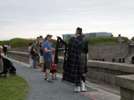 Visitors converse with a bagpipe player at Citadel National Historic site, a star-shaped fortress overlooking the harbor in Halifax, Nova Scotia.