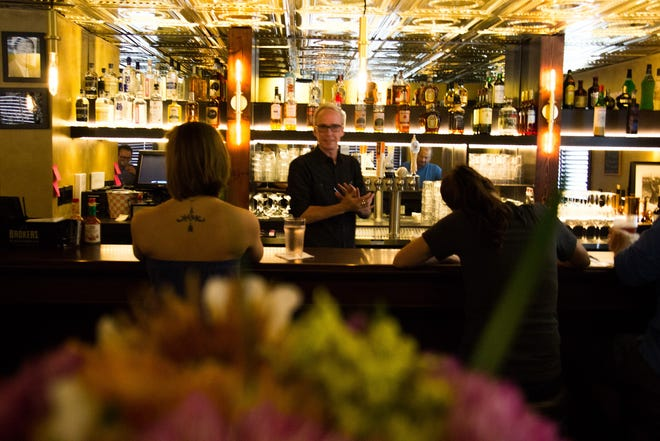 Bartender Ian Roach speaks with customers on the first day of business at The Corner Lounge on Sept. 25, 2018.