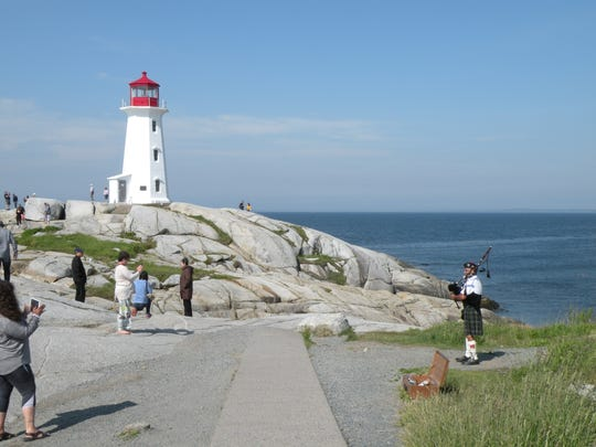 A busker playing bagpipes entertains visitors photographing the lighthouse at Peggy's Cove, Nova Scotia. The province has more than 160 lighthouses.