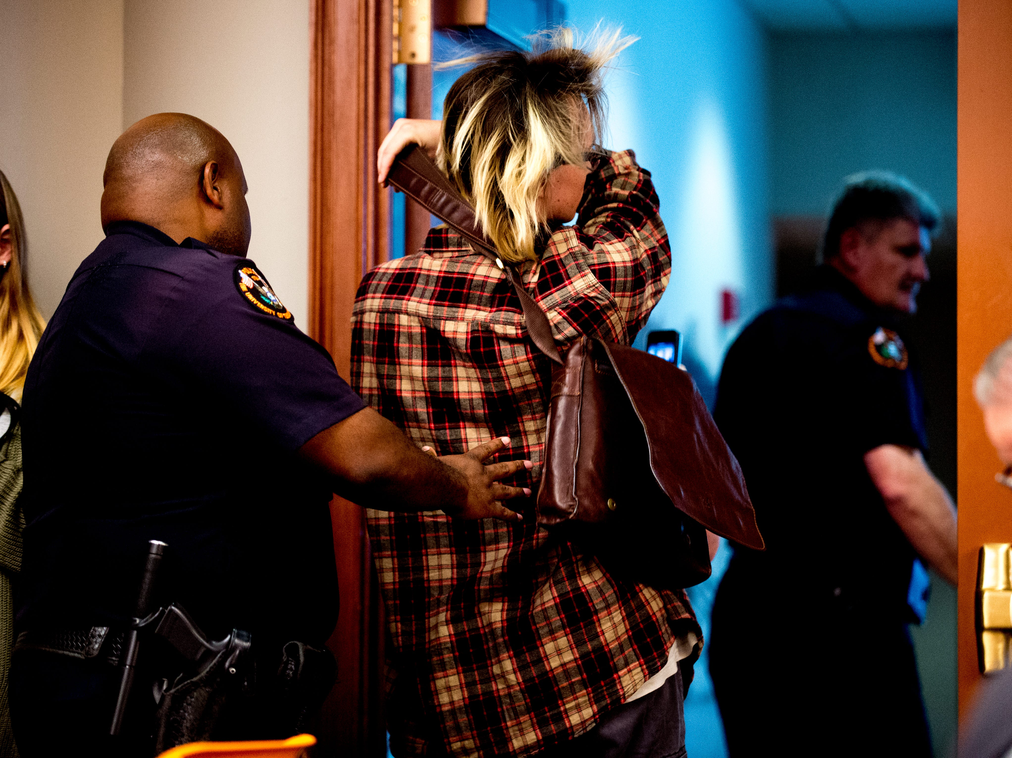 A protestor is escorted out of the room by UTK police officers after interrupting the proceedings during a University of Tennessee Board of Trustees meeting at the UTK Visitor's Center in Knoxville, Tennessee on Tuesday, September 25, 2018. The board met to discuss several topics including the installment of an interim president.