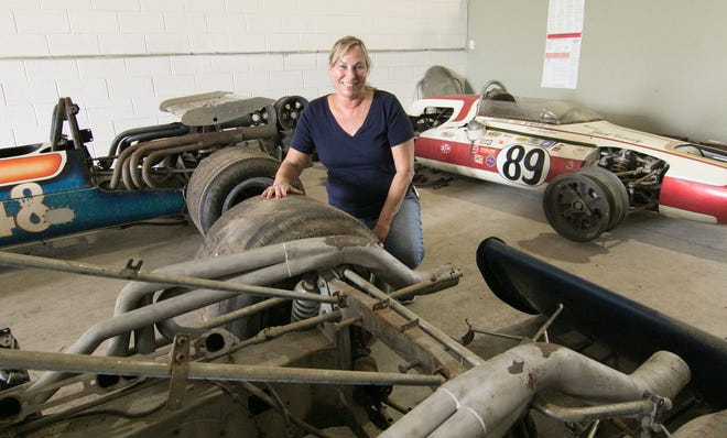 Jeri Conely-Tunell poses Tuesday, Sept. 25, 2018 between three race cars her father Jack Conely competed with, stored in a Green Oak Township warehouse in preparation for an auction of all the cars and parts amassed in his race career. Behind Conely-Tunell, no. 89 was the car her father qualified in at the Indianapolis 500.