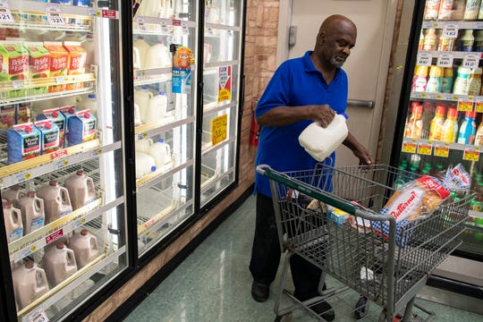 A customer buys a gallon of milk in the Cash Saver grocery store on Wilson Avenue. Sept. 25, 2018
