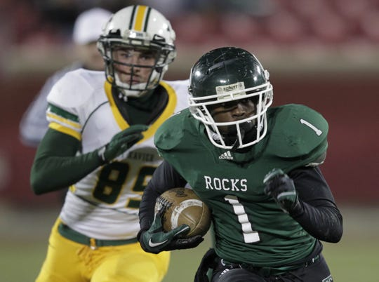 Trinity High School Dalyn Dawkins (1) fights to break free from St. Xavier's Corey Smith (85) during the second half of their regional football championship game at Papa John's Stadium in Louisville, Kentucky.      November 18, 2011