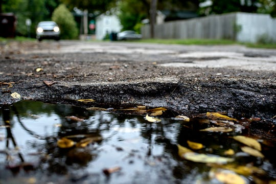 A pothole filled with water seen on Marcus Street near Fairview Avenue on Monday, Sept. 24, 2018, in Lansing.