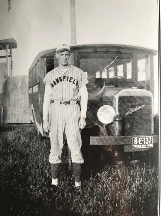 Fred Wolpert, a pitcher for the 1941 Mansfield Braves, models the team's road uniform in front of the team bus, a broken-down 1926 Reo Speedwagon, which the Braves would comically push up hills and then chase after as it rolled downhill.