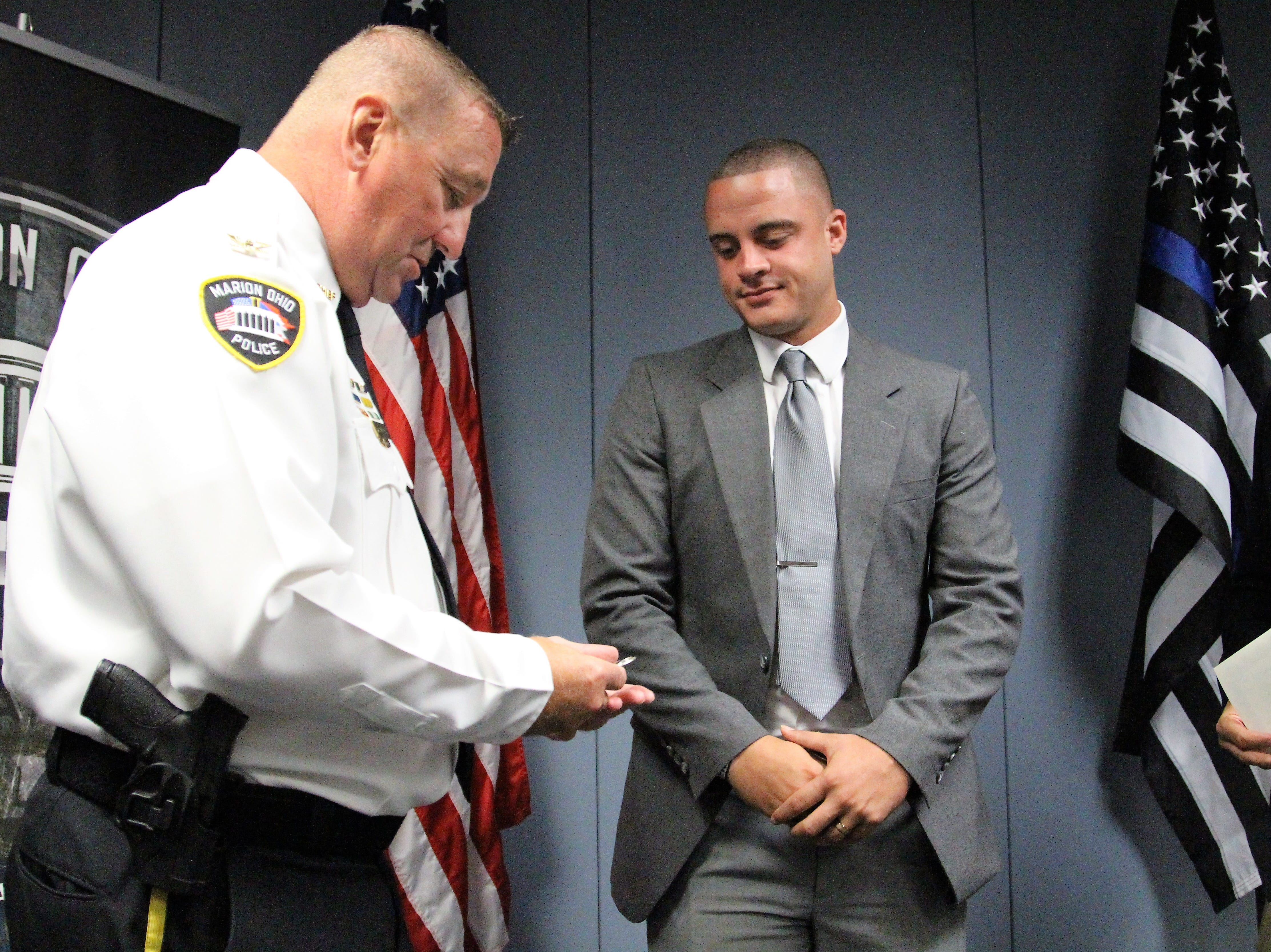 Marion Police Chief Bill Collins prepares to hand new hire Sebastian Walker his police badge during a Monday afternoon ceremony.