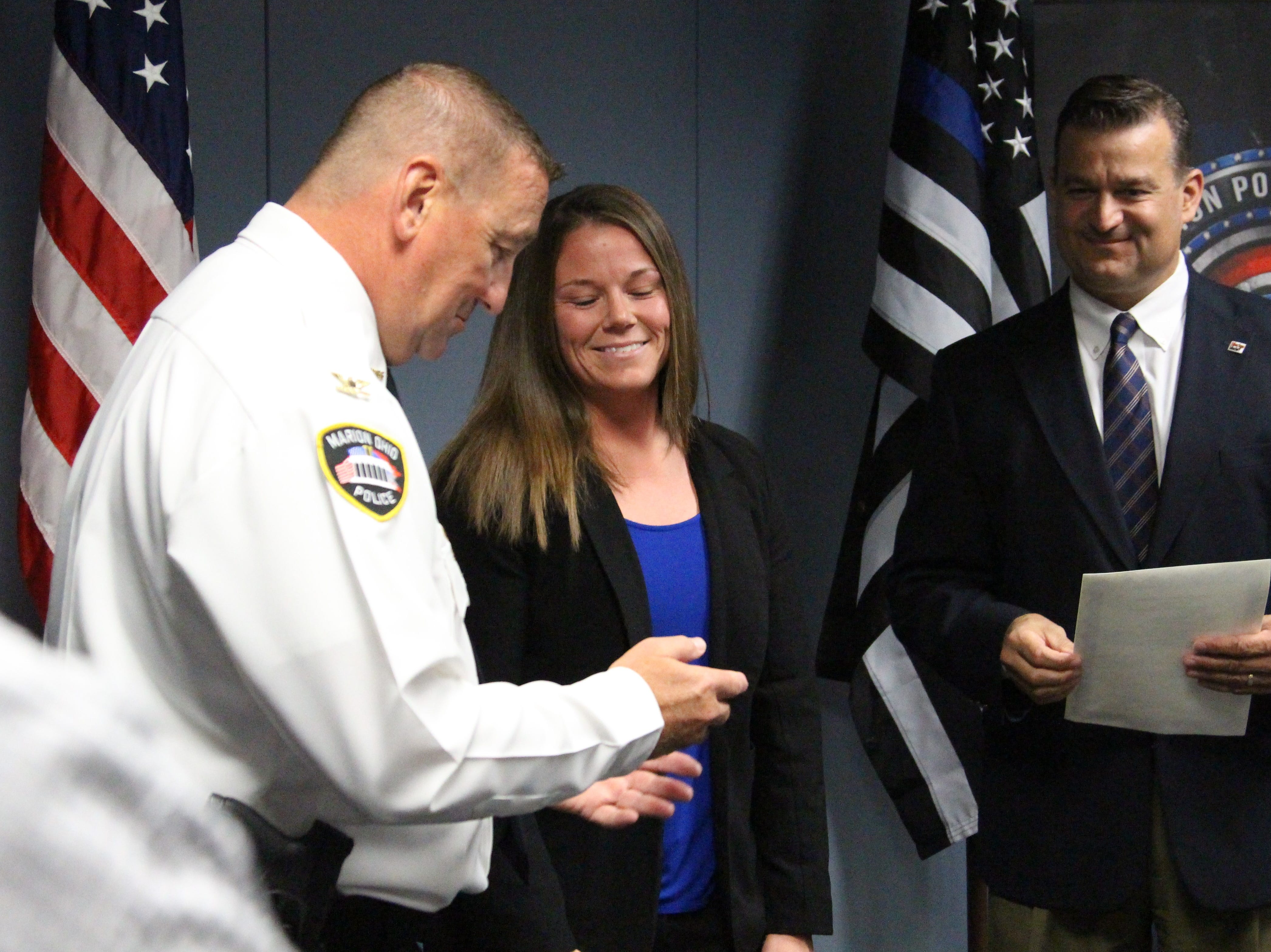 Dena Benroth looks at her new badge that will be pinned to her shirt by a loved one during a ceremony on Monday that welcomed four new officers to the Marion Police Department.