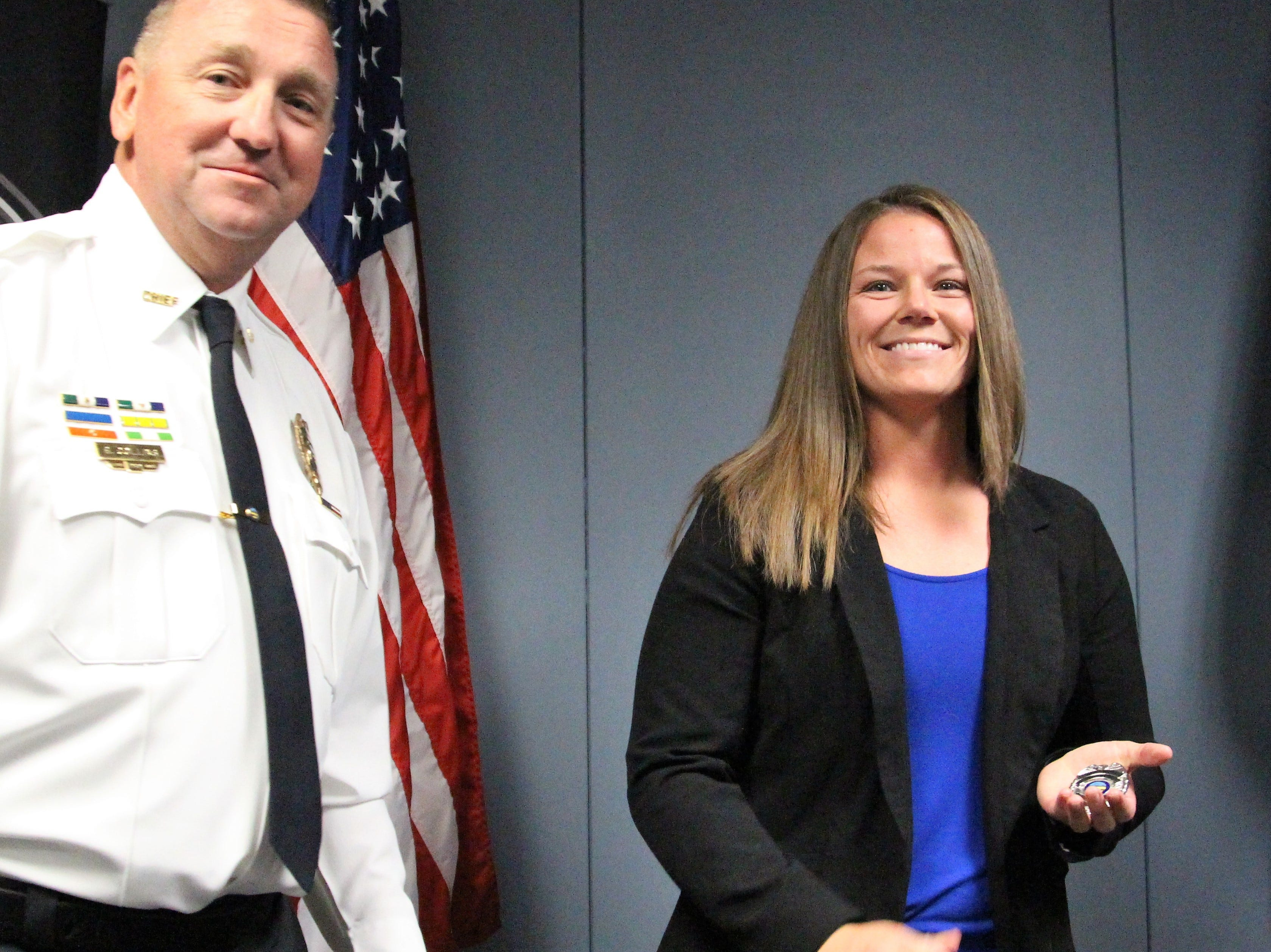 Dena Benroth holds her new badge after being issued the oath of office by Mayor Scott Schertzer on Monday.