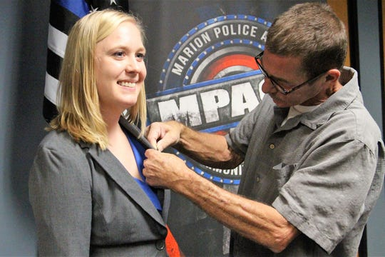 Eric Meadows pins a police badge onto his daughter Kaitlyn's jacket during a ceremony last year that saw four recruits being sworn into the Marion Police Department.