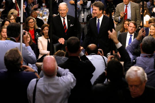 Supreme Court nominee Judge Brett Kavanaugh is surrounded by photographers as he stands with Senate Judiciary Committee Chairman Chuck Grassley R-Iowa, on Sept. 4,  during Kavanaugh's confirmation hearing on Capitol Hill in Washington.