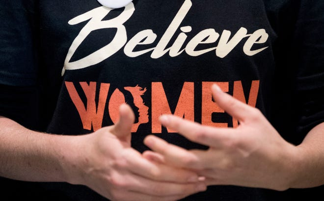 "A woman wears a shirt that reads ""Believe Women"" with a button that reads ""I Believe Dr. Christine Blasey Ford""."
