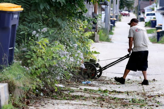 Trey Hernandez of Sidello Asset Management, a City of West Allis subcontractor, uses a walk-behind string trimmer to cut through undergrowth on the alley side of one of four properties he is to cut within two blocks of South 58th Street on Sept. 25.