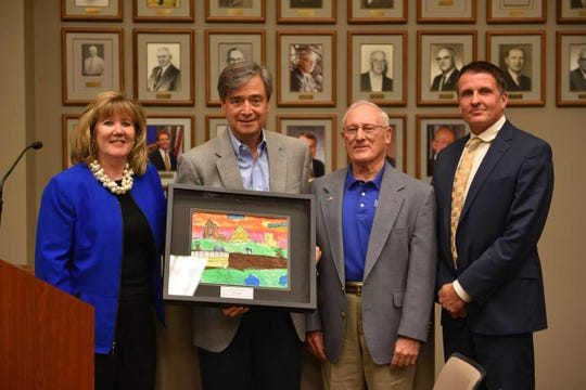 Outgoing Menomonee Falls School Board member Michael Vettor (second from left) accepts the Friends of Education Award, a student-created landscape painting, at the Menomonee Falls School Board's Sept. 24 meeting.