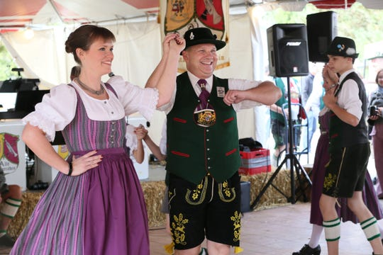 """Lauren Forster (left) and Joey Schiller (center right) and fellow members of Wendlstoana Milwaukee, a German dance club founded in Milwaukee in 1927, perform traditional Bavarian dance in a style called """"schuplatting"""" or slap dancing at Cedarburg's 2016 Oktoberfest. This year's festivities are Saturday, Oct. 13 and Sunday, Oct. 14."""