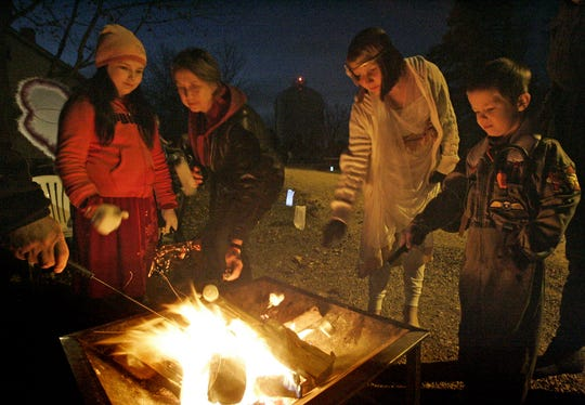 Guests at a past Halloween Family Fun night at the Old Falls Village roast marshmallows around a fire.