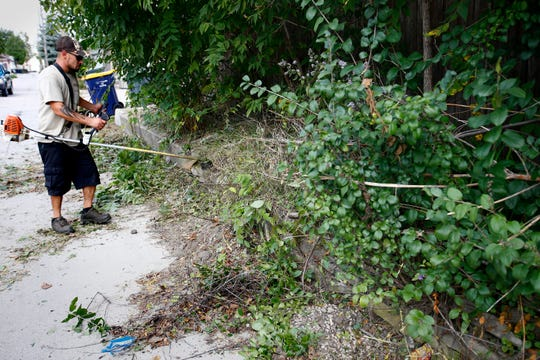 Trey Hernandez of Sidello Asset Management, a city of West Allis subcontractor, uses a string trimmer to cut undergrowth on the alley side of one of four properties he is to cut within two blocks of South 58th Street on Sept. 25.