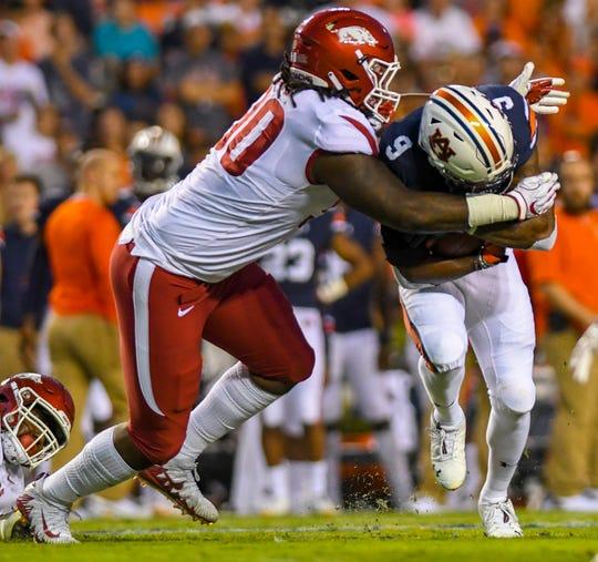 Arkansas defensive lineman Armon Watts (90) wraps up Auburn running back Kam Martin (9) during the first quarter Saturday, Sept. 22, 2018, at Jordan-Hare Stadium in Auburn, Ala. (Julie Bennett/Montgomery Advertiser)