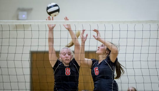 Wapahani senior setter Ali Stewart goes up for a block with former Raider Estella Davis during a match against Muncie Central on Sept. 24, 2018.