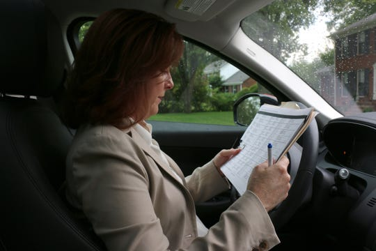 State House candidate Rebecca Purington looks through the addresses of voters in a Brentwood neighborhood as she knocks on doors Sept. 13, 2018.
