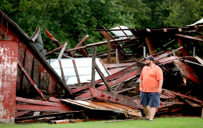 Steven Patterson looks over the storm damage to his mother-in-law, Linda Holland's barn in the Readyville community, on Monday Sept. 24, 2018.  People were in the barn when the wind knocked it down but there were no injuries.