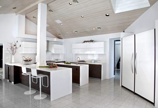 This kitchen in Alpine, designed by Kuche+Cucina in Paramus, features high-gloss white lacquer floating wall cabinets and a quartz Caesarstone backsplash.