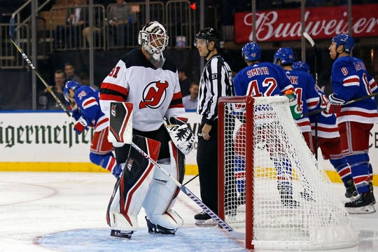 New Jersey Devils goaltender Eddie Lack, front left, reacts after giving up a goal to New York Rangers' Steven Fogarty (38) in the second period of a preseason NHL hockey game Monday, Sept. 24, 2018, in New York.