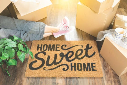 Woman Wearing Sweats Relaxing Near Home Sweet Home Welcome Mat Moving Boxes And Plant