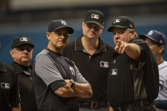 New York Yankees manager Aaron Boone (17) talks to umpires Jerry Layne, Jordan Baker, Greg Gibson and Vic Carapazza before a game against the Tampa Bay Rays at Tropicana Field.