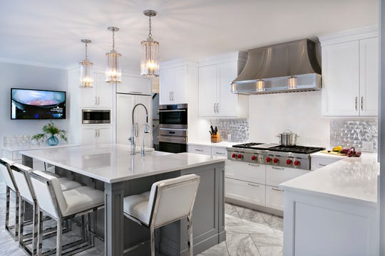 This kitchen in Tenafly, designed by Ulrich in Ridgewood, features an aluminum silver metal tile backsplash from Bergen Brick & Tile in Wyckoff and DuraCeramic Carrara white floor tiles.
