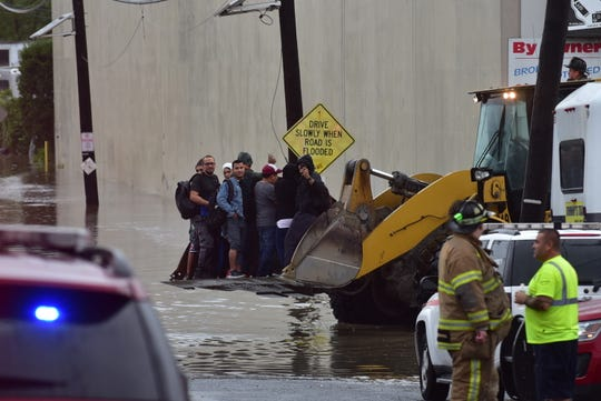 Rescue personnel evacuate stranded workers with a bulldozer after high water flooded the surrounding streets at an Industrial Park in Fairview.