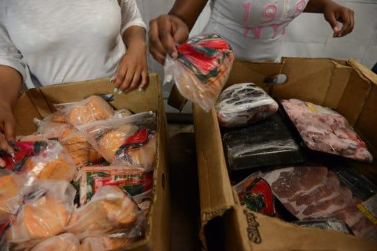 Jessica Williams and Rasheema Davis sort frozen meats at CUMAC in 2014.