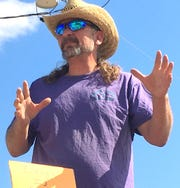 Mike Reitz, director of DAGship, addressed the protest crowd from the bed of a truck on Saturday.