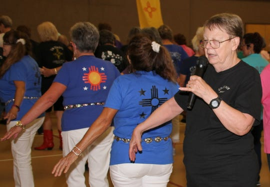 Joyce Peterson, of the Zia Zingers, directed traffic and called out dance moves during the line dance jamboree on Saturday.
