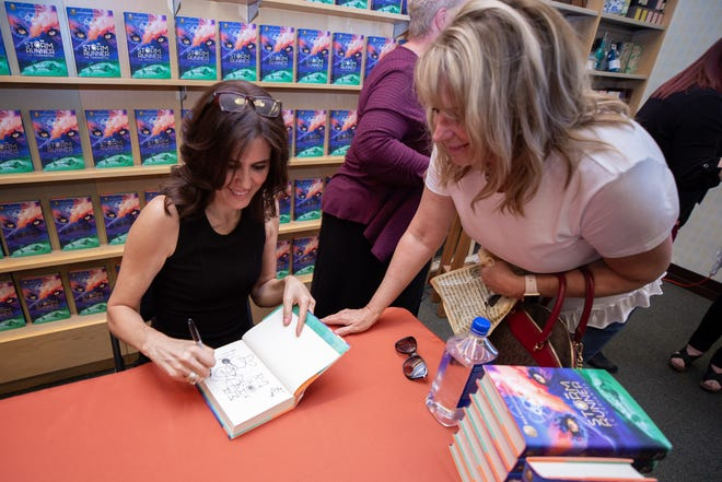 "Jennifer Cervantes signs her book, ""Storm Runner"" for Kelley Coffeen during the book-signing event on September 22, 2018."