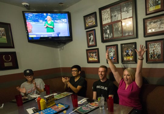 Kristy McDougall, right, cheers along side her son Chase McDougall, left, as friends and family join her to watch her compete on the game show wheel of fortune, Monday September 24, 2018 at The Game Bar and Grill.
