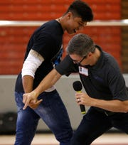 Master of ceremonies Matt Meuleners, right, a managing partner with FOCUS Training, plays a game with Shiprock High School junior Adam Requiman Tuesday during a rally for Gaining Early Awareness and Readiness for Undergraduate Programs at the Chieftain Pit in Shiprock.