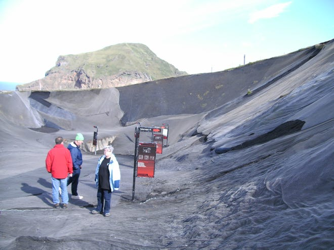 Tourists hike on a Icelandic volcano crater on the Surtsey Island.