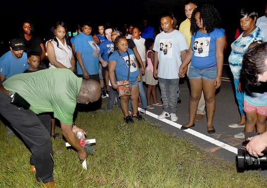 Mayor Reggie Tatum places a crucifix at the site where Diamonesha Guillory was killed by a hit and run driver recently on the Interstate 49 Service Road just south of Opelousas. A vigil for the 17 year old was held Wednesday, Sept. 19, at the site of the accident. See more photos on the Daily World Facebook site.