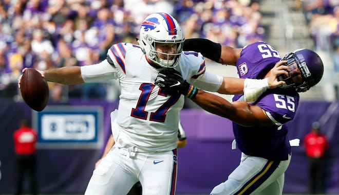 Buffalo Bills quarterback Josh Allen tries to break a tackle by Minnesota Vikings linebacker Anthony Barr (55) during the first half of an NFL football game, Sunday, Sept. 23, 2018, in Minneapolis. (AP Photo/Bruce Kluckhohn)
