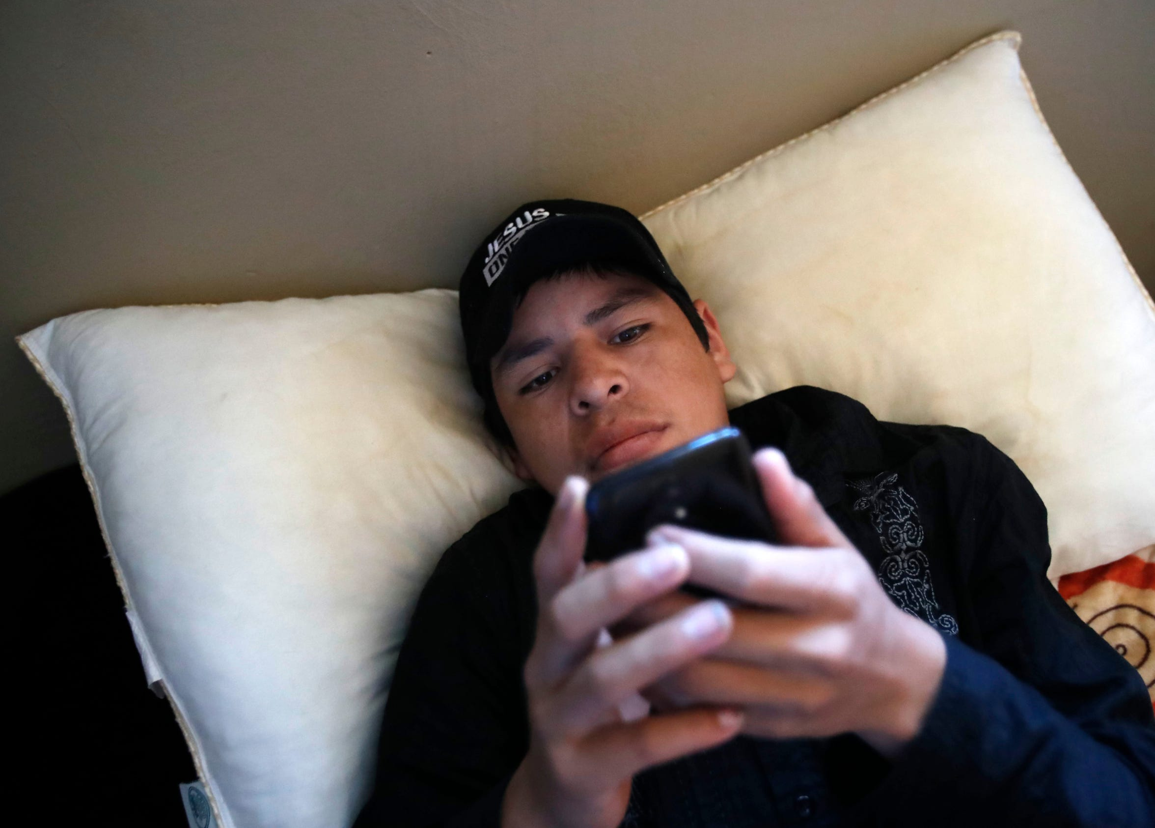 Artemio plays with his phone one morning at home. Artemio, now 18, spent 11 months in immigrant child detention centers in San Diego and New York.