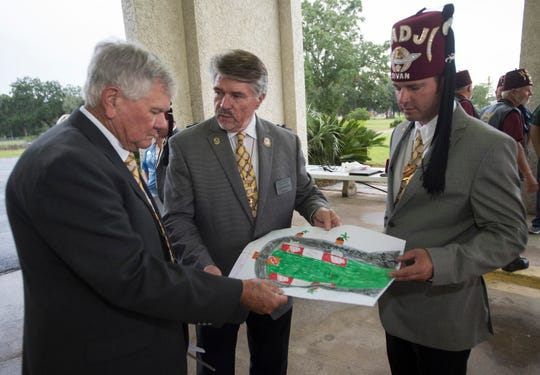 Larry Mills, Carlos Baxley and Travis High review plans for garden and green space surrounding the organization's new Silent Messenger statue outside the West Nine Mile Road Temple on Monday, Sept. 24, 2018