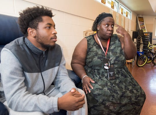 Evelyn Webber, the program director for at-risk youths at the Dorrie Miller Community Center, describes her mission to keep children out of trouble while, Keyon English, a former participant in the program, looks on.