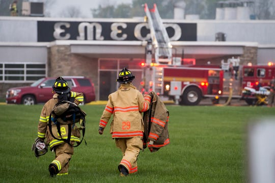 Two firefighters with Southeastern Adams Volunteer Emergency Services Company 29 walk toward the scene of a working commercial fire at Emeco Industries in Conewago Township September 25, 2018.