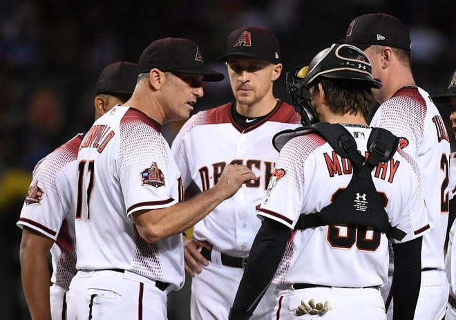 Manager Torey Lovullo #17 of the Arizona Diamondbacks talks with Nick Ahmed #13, John Ryan Murphy #36 and teammates on the mound during the seventh inning against the Los Angeles Dodgers at Chase Field on September 24, 2018 in Phoenix, Arizona.