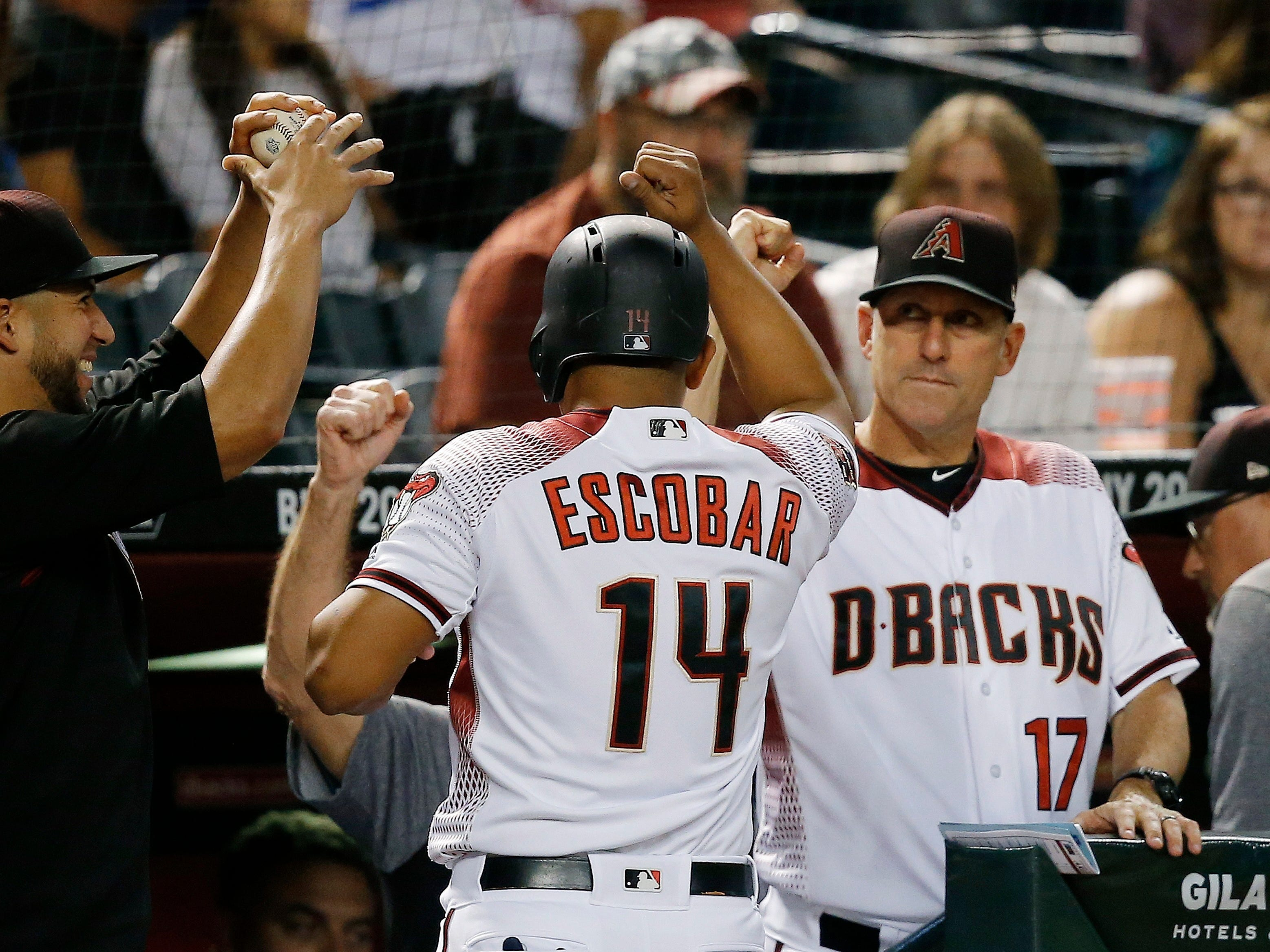 Arizona Diamondbacks' Eduardo Escobar (14) celebrates his run scored against the Los Angeles Dodgers with David Peralta, left, and manager Torey Lovullo (17) during the first inning of a baseball game, Monday, Sept. 24, 2018, in Phoenix. (AP Photo/Ross D. Franklin)
